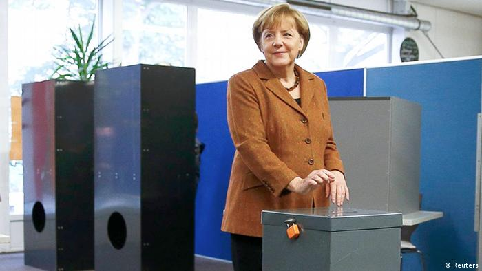 German Chancellor Angela Merkel poses as she casts her ballot during the German general election (Bundestagswahl) at a polling station in Berlin, September 22, 2013. The person at left is Merkel's husband Joachim Sauer. REUTERS/Kai Pfaffenbach (GERMANY - Tags: POLITICS ELECTIONS) ***FREI FÜR SOCIAL MEDIA***