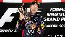 SINGAPORE - SEPTEMBER 22: Sebastian Vettel of Germany and Infiniti Red Bull racing lifts the trophy following his victory during the Singapore Formula One Grand Prix at Marina Bay Street Circuit on September 22, 2013 in Singapore, Singapore. (Photo by Mark Thompson/Getty Images)