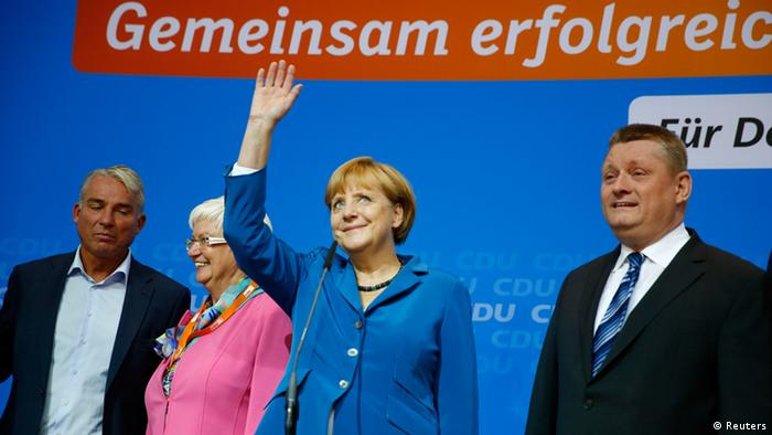 German Chancellor and leader of Christian Democratic Union (CDU) Angela Merkel waves as she arrives to address supporters after first exit polls in the German general election (Bundestagswahl) at the CDU party headquarters in Berlin September 22, 2013. Merkel's conservatives won the most votes in a German election on Sunday, putting her on track for a third term, but it was unclear whether she would be able to preserve her centre-right coalition or be forced to work with her leftist rivals, an exit poll showed. At right is CDU party secretary general Hermann Groehe, and at left is Thomas Strobl, leader of the Christian Democratic Union (CDU) in Baden-Wuerttemberg . REUTERS/Kai Pfaffenbach (GERMANY - Tags: POLITICS ELECTIONS)