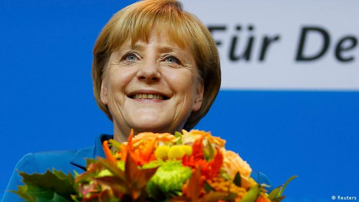 German Chancellor and leader of the Christian Democratic Union (CDU) Angela Merkel smiles as she holds flowers after first exit polls in the German general election (Bundestagswahl) at the party headquarters in Berlin September 22, 2013. REUTERS/Kai Pfaffenbach (GERMANY - Tags: POLITICS ELECTIONS)