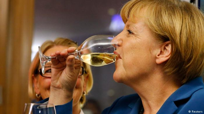 German Chancellor and leader of the Christian Democratic Union (CDU) Angela Merkel drinks a glass of wine as she celebrates after first exit polls in the German general election (Bundestagswahl) at the CDU party headquarters in Berlin September 22, 2013. Merkel won a landslide personal victory in a German election on Sunday, putting her within reach of the first absolute majority in parliament in half a century, a ringing endorsement of her steady leadership in the euro crisis. REUTERS/Fabrizio Bensch (GERMANY - Tags: POLITICS ELECTIONS)
