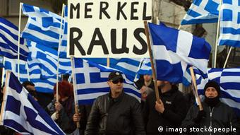 Greek protesters hold a sign demanding Merkel leave the country