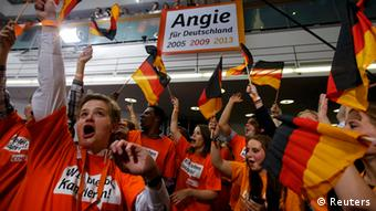 Supporters of the Christian Democratic Union (CDU) celebrate after first exit polls in the German general election (Bundestagswahl) at the CDU party headquarters in Berlin September 22, 2013. Chancellor Angela Merkel won a landslide personal victory in a German election on Sunday, putting her within reach of the first absolute majority in parliament in half a century, a ringing endorsement of her steady leadership in the euro crisis. REUTERS/Fabrizio Bensch (GERMANY - Tags: POLITICS ELECTIONS)