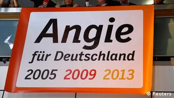 Supporters of the Christian Democratic Union (CDU) stand on a balcony behind a banner reading 'Angie', the nickname of German Chancellor and conservative Christian Democratic Union (CDU) leader Angela Merkel, as they celebrates after first exit polls in the German general election (Bundestagswahl) at the CDU party headquarters in Berlin September 22, 2013. Chancellor Angela Merkel won a landslide personal victory in a German election on Sunday, putting her within reach of the first absolute majority in parliament in half a century, a ringing endorsement of her steady leadership in the euro crisis. REUTERS/Kai Pfaffenbach (GERMANY - Tags: POLITICS ELECTIONS)
