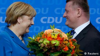 German Chancellor and leader of the Christian Democratic Union (CDU) Angela Merkel smiles as she receives flowers from Hermann Groehe (R), CDU secretary general, after first exit polls in the German general election (Bundestagswahl) at the party headquarters in Berlin September 22, 2013. REUTERS/Fabrizio Bensch (GERMANY - Tags: POLITICS ELECTIONS)