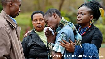 A man only identified by his first name, Stephen (C) is comforted by Pastor Elizabeth Akinyi (R) and family members at the city mortuary in Nairobi on September 23, 2013. Stephen's father was killed in the Westgate mall siege on September 21, 2013. Kenyan Defence troops remain inside the mall, in a standoff with Somali militants after they laid siege to the shopping centre shooting and throwing grenades as they entered. AFP PHOTO/Carl de Souza (Photo credit should read CARL DE SOUZA/AFP/Getty Images)