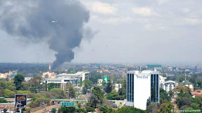A helicopte and birds fly above as a plume of black smoke billows rising over the Westgate Mall, following large explosions and heavy gunfire, in Nairobi, Kenya Monday, Sept. 23, 2013. Four large blasts rocked Kenya's Westgate Mall on Monday, sending large plumes of smoke over an upscale suburb as Kenyan military forces sought to rescue an unknown number of hostages held by al-Qaida-linked militants. (AP Photo/Riccardo Gangale) ***FREI FÜR SOCIAL MEDIA***