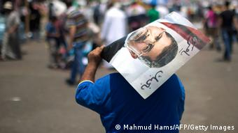 An Egyptian supporter of the Muslim Brotherhood walks holding a poster featuring deposed president Mohamed Morsi during a rally to support him on July 6, 2013 outside Cairo's Rabaa al-Adawiya mosque. Egypt's Islamists vowed further protests today to demand the army restore the country's first democratically elected leader, after a day of clashes which saw 26 people killed across the country. AFP PHOTO/MAHMUD HAMS (Photo credit should read MAHMUD HAMS/AFP/Getty Images)