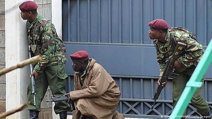 Armed Kenyan policemen take cover outside the Westgate mall in Nairobi on September 23, 2013. Kenyan troops were locked in a fierce firefight with Somali militants inside an upmarket Nairobi shopping mall on September 22 in a final push to end a siege that has left at least 69 dead and 200 wounded with an unknown number of hostages still being held. Somalia's Al Qaeda-inspired Shebab rebels said the carnage at the part Israeli-owned complex mall was in retaliation for Kenya's military intervention in Somalia, where African Union troops are battling the Islamists. Photo: SIMON MAINA/AFP/Getty Images