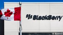 A Canadian flag waves in front of a Blackberry logo at the Blackberry campus in Waterloo, September 23, 2013. REUTERS/Mark Blinch (CANADA - Tags: BUSINESS EMPLOYMENT LOGO)