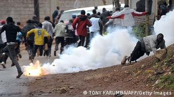 Africans run from a flaming, smoking object on the street.