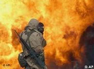 Journalist mit Kamera vor brennendem Ölfeld im Irakkrieg