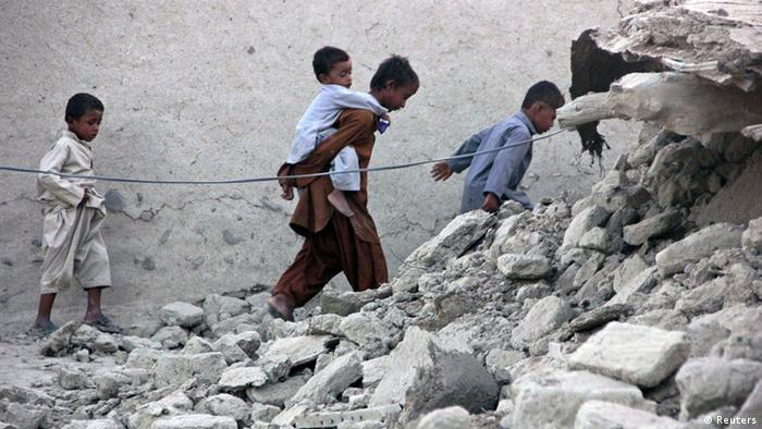 Survivors of an earthquake walk on rubble of a mud house after it collapsed following the quake in the town of Awaran, southwestern Pakistani province of Baluchistan, September 25, 2013. The death toll from a powerful earthquake in Pakistan rose to at least 208 on Wednesday after hundreds of mud houses collapsed on people in a remote area near the Iranian border, officials said. REUTERS/Sallah Jan (PAKISTAN - Tags: DISASTER)