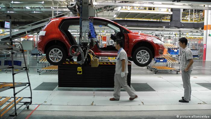 Chinesische Arbeiter stehen am 25.09.2013 an der Fertigungsstraße für den neuen Golf im neu eröffneten Volkswagen Werk in der südchinesischen Metropole Foshan.