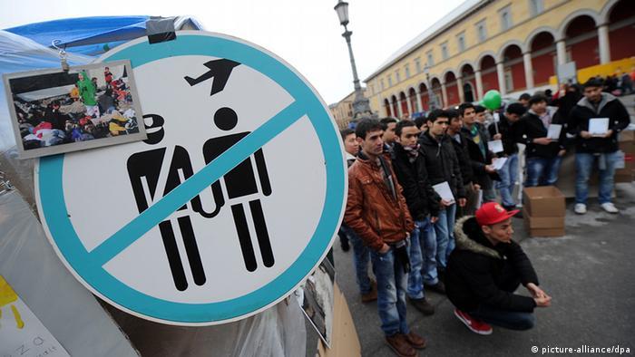 Afghanische Flüchtlinge stehen am 22.12.2012 in München bei einer Kundgebung zusammen während im Vordergrund ein Schild zu sehen ist, das als Piktogramm einen Polizisten, einen Mann mit Handschellen und ein Flugzeug zeigt (Foto: Tobias Hase/dpa)