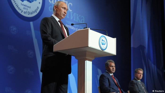 On stage, a caucasian politician in a business suit speaks into the microphone of a podium in front of a blue backdrop. (Photo: Alexey Druzhinin)
