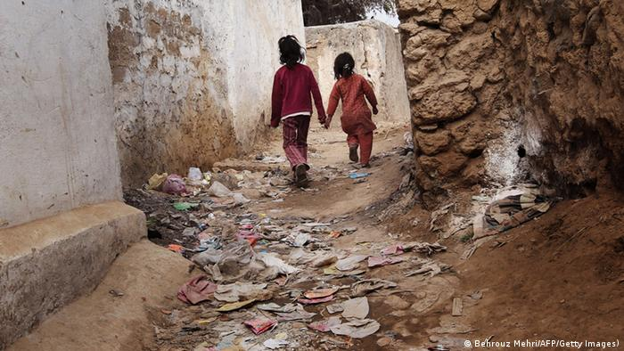 Pakistani children walk down a garbage strewn alley in a poor neighbourhood of Islamabad on January 27, 2010