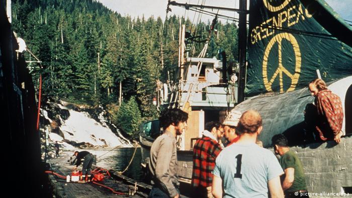 Aktivisten stehen vor einem Fischkutter mit grünem Segel auf dem das Peace-Zeichen und der Schriftzug Greenpeace geschrieben steht. (picture-alliance/dpa)