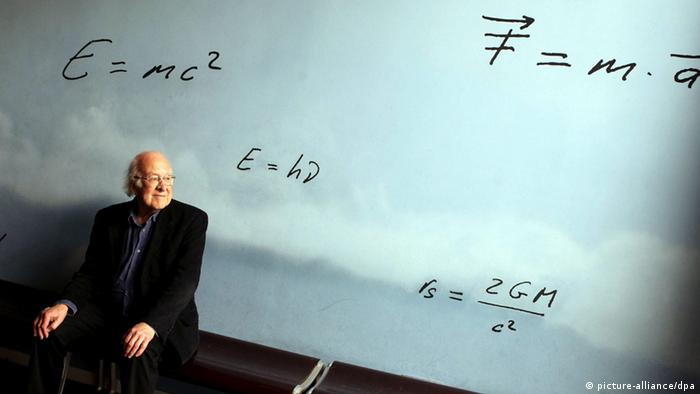 British physicist Peter Higgs sits in front of a wall with famous equations, E=mc2, written on it