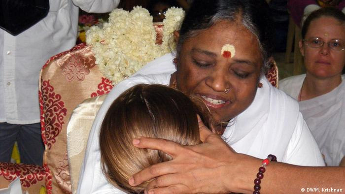 Ma Amritanandamayi is seen hugging a devotee. Many say her hug radiates energy and they find solace. DW/Murali Krishnan