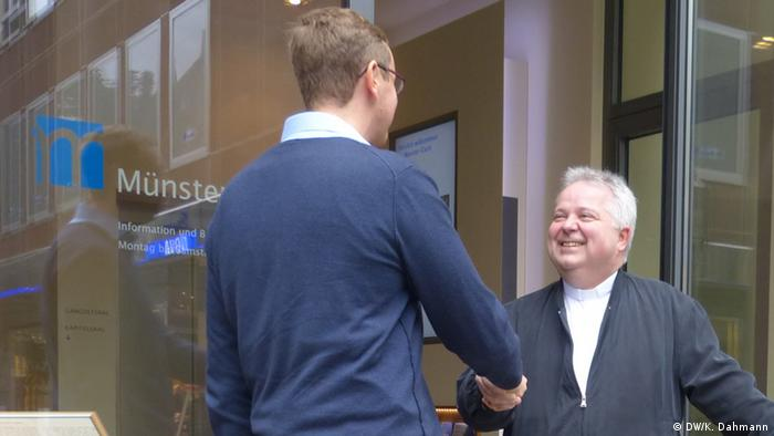 Der katholische Pfarrer Thomas Bernards begrüßt einen Besucher am Eingang der Kircheneintrittsstelle FIDES im Bonner Münster-Carré. - Copyright: DW/K. Dahmann