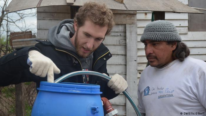 Diego Musolino (left) explains to Pablo Uviedo how to fill a solar water heater (Photo: Eilis O'Neill)