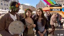 Drei Personen mit Blumenkränzen im Haar stehen in Wittenberg auf dem Marktplatz.