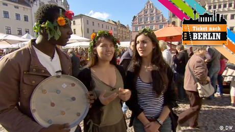 Drei Teilnehmer von Ticket nach Berlin stehen auf einem Marktplatz. (DW)