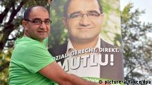 Der Direktkandidat des Bündnis 90/Die Grünen für Mitte, Özcan Mutlu, hängt am 04.08.2013 in Berlin Wahlplakate auf. Foto: Britta Pedersen/dpa