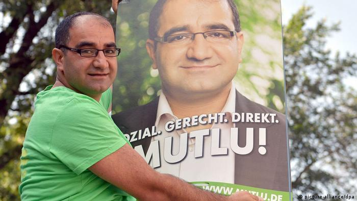 Özcan Mutlu hanging up a campaign poster in Berlin (Photo: Britta Pedersen/dpa)