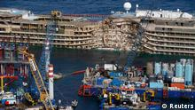 The capsized cruise liner Costa Concordia is seen at the end of the parbuckling operation outside Giglio harbour September 17, 2013. Salvage crews completed raising the wreck of the Costa Concordia in the early hours of Tuesday morning after a 19-hour-long operation on the Italian island of Giglio where the huge cruise liner capsized in January last year. REUTERS/Tony Gentile (ITALY - Tags: DISASTER MARITIME SOCIETY)