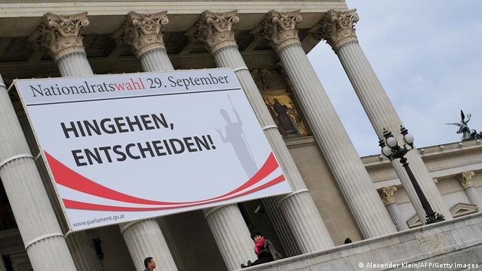 GettyImages 181420009 Tourists take pictures in front of the Austrian parliament on September 21, 2013 in Vienna, Austria, under a banner that reads 'Go there, decide' . Austrian legislative elections will be held on September 29, 2013. AFP PHOTO / ALEXANDER KLEIN (Photo credit should read ALEXANDER KLEIN/AFP/Getty Images)