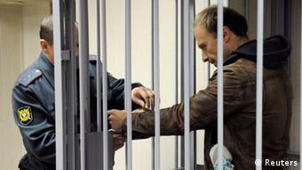 Photographer Denis Sinyakov, one of the 30 people detained after a Greenpeace protest at the Prirazlomnaya platform, has his handcuffs removed inside a defendants' box at a district court building in Murmansk, (Photo: REUTERS/Sergei Eshchenko (RUSSIA)