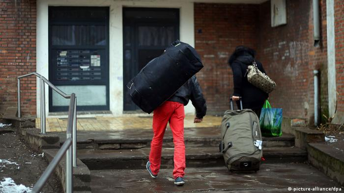 A man with a duffel bag over his shoulder and a woman carrying a suitcase enter a run-down brick building