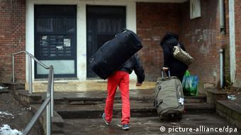 A man with red trousers and a black bag walks into a house (Foto: Oliver Berg/dpa)