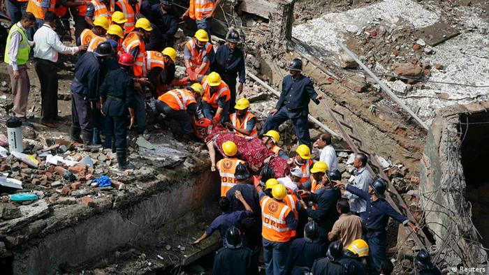 Rescue workers recover a body from the debris at the site of a collapsed residential building in Mumbai September 27, 2013. One person was killed and six injured when the five-storey building came crashing down in south Mumbai on Friday morning, local media quoted officials as saying. REUTERS/Danish Siddiqui (INDIA - Tags: DISASTER) TEMPLATE OUT