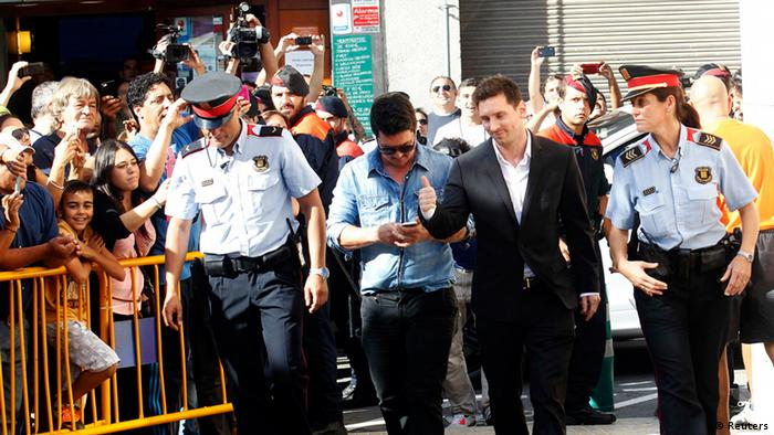 Barcelona forward Lionel Messi (2nd R) gives a thumbs up as he arrives in court to answer charges of tax evasion in Gava September 27, 2013. Barcelona's soccer player Messi and his father Jorge have paid five million euros ($6.6 million) as a corrective payment to the Spanish authorities after they were accused in June of filing false tax returns, a court statement said on September 4. REUTERS/Albert Gea