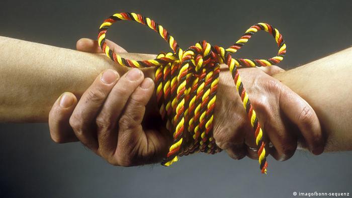 Две руки, перевязанные шнурком в цветах немецкого флага