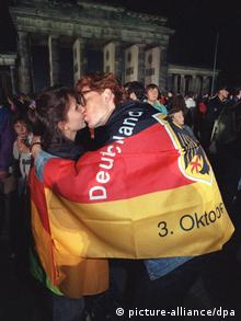 Wrapped in a German flag, two Germans kiss in front of the Brandenburg Gate and celebrate the reunification of Germany in 1990