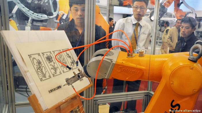 Visitors watch a robot arm of Staubli drawing during the 14th China International Industry Fair 2012 in Shanghai, China, 6 November 2012. A total of 1,648 companies from home and abroad participate in the 14th China International Industry Fair which is being held from November 6 to 10 at the Shanghai New International Expo Centre.