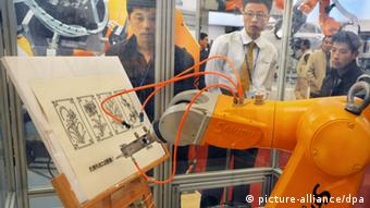 Visitors watch a robot arm of Staubli drawing during the 14th China International Industry Fair 2012 in Shanghai, China, 6 November 2012.