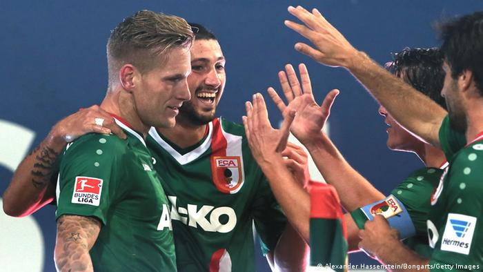 AUGSBURG, GERMANY - SEPTEMBER 27: Andre Hahn (L) of Augsburg celebrates scoring the opening goal with his team mate Sascha Moelders (2nd L) and others during the Bundesliga match between FC Augsburg and Borussia Moenchengladbach at SGL Arena on September 27, 2013 in Augsburg, Germany. (Photo by Alexander Hassenstein/Bongarts/Getty Images)