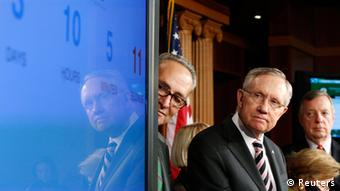 U.S. Senate Majority Leader Harry Reid (D-NV) (3rd R) looks at a screen showing a clock counting down to a government shutdown, at a news conference with fellow Democrats Senator Chuck Schumer (D-NY) (4th R), Senator Barbara Mikulski (D-MD) (2nd R) and Senator Dick Durbin (D-IL) (R) after the Senate voted to pass a spending bill in an attempt to avoid the shutdown, sending the issue back to the House of Representatives, at the U.S. Capitol in Washington September 27, 2013. The U.S. government braced on Friday for the possibility of a partial shutdown of operations on October 1 as Congress struggled to pass an emergency spending bill that Republicans want to use to defund the new healthcare reform law. REUTERS/Jonathan Ernst (UNITED STATES - Tags: POLITICS BUSINESS TPX IMAGES OF THE DAY)