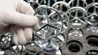 Ein DaimlerChrysler Mitarbeiter hält im Mercedes-Werk in Sindelfingen (bei Stuttgart) am Mittwoch (09.02.2005) mit weißen Handschuhen einen Mercedes Stern in der Hand p178 Symbolfoto