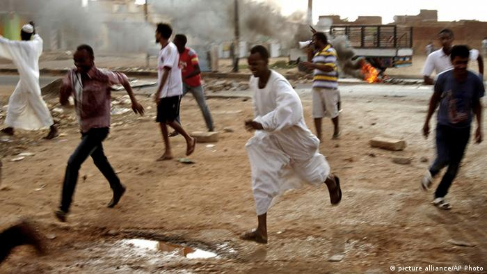 In this Friday, Sept. 27, 2013 photo, Sudanese protesters run from riot police during clashes in Khartoum, Sudan. The regime of President Omar al-Bashir is trying to stop public anger over fuel price hikes from turning into an Arab Spring-style uprising against his 24-year rule. (AP Photo/Abd Raouf)