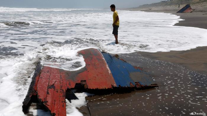REFILE - CORRECTING NAME OF CLOSEST CITY A youth stands near a piece of wreckage of a boat which sank off the Indonesian coast, at Agrabinta beach on the outskirts of Sukabumi, Indonesia's West Java province September 28, 2013. The boat carrying migrants to Australia sank off the Indonesian coast on Friday, killing at least 21 people, Indonesian police said, a sign that Australia's tough new immigration rules may not be enough to deter would-be asylum seekers. REUTERS/Beawiharta (INDONESIA - Tags: DISASTER POLITICS SOCIETY IMMIGRATION)