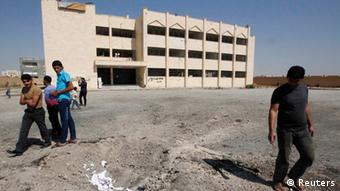 People walking past destroyed school in Raqqa in eastern Syria (Photo: REUTERS/Nour Fourat)