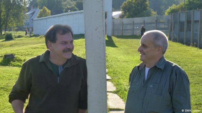 Die beiden Jäger Klaus Staltmair (l.), früher Bundeswehrsoldat, und Lothar Bauer, ehemals DDR-Grenztruppen-Angehöriger stehen an der Mauer des geteilten Dorfes Mödlareuth - Foto: Karin Jäger (DW)