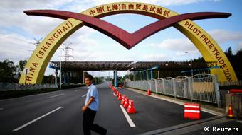 A man walks past a welcoming sign of the newly announced Shanghai Free Trade Zone in Shanghai in this September 25, 2013 file photo. China's leaders will lay out plans to transform the world's second-largest economy at a key party meeting in November, leaving the question of how to do it largely unanswered as much of the reform agenda is still a matter of heated internal debate. To match CHINA-ECONOMY/REFORMS REUTERS/Carlos Barria/Files (CHINA - Tags: POLITICS BUSINESS)