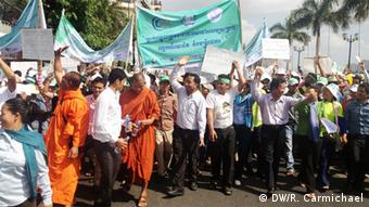 Buddhist monks and union leaders wave to construction workers as they pass a building site during this year's May Day march by thousands of workers through Phnom Penh.